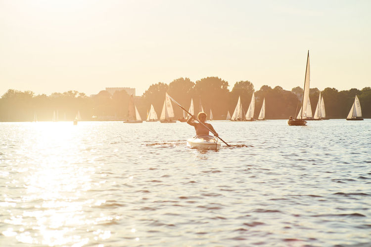 Mid Adult Woman Canoeing On Sea Against Clear Sky During Sunset