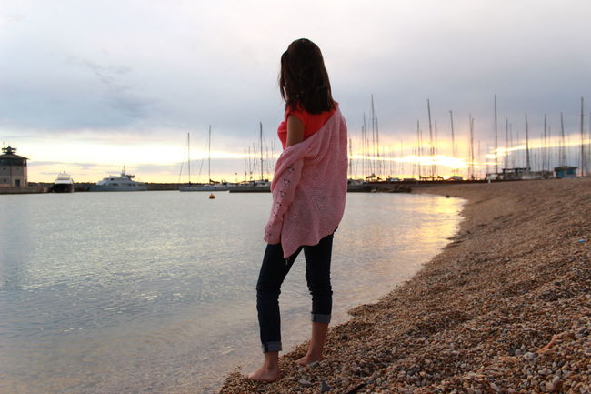 Looking far far away for someting better. Beauty In Nature Boats And Sea Casual Clothing Getting Away From It All Nautical Vessel One Person On Beach Pink Hoodie Seaport Of Ostia Stones On A Beech Scene Sun Behind The Clouds Very Cloude Sky Water Of Sea