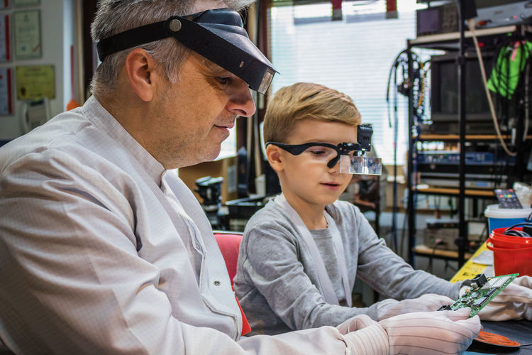 Man with boy examining computer part