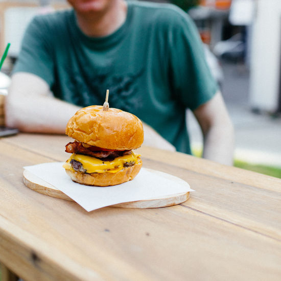 Close-up of hamburger with man sitting in background
