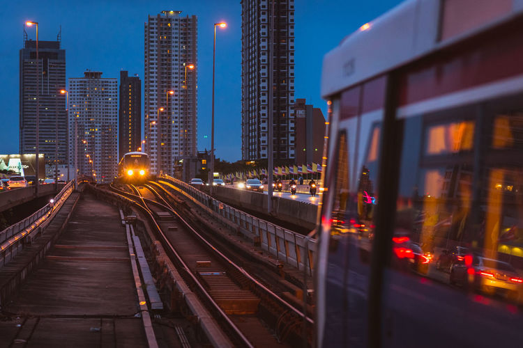 Illuminated railroad tracks amidst buildings in city at night
