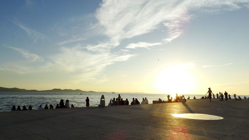 Summer In The City Adult Beach Beauty In Nature Crowd Group Of People Land Large Group Of People Leisure Activity Lifestyles Nature Outdoors Promenade Real People Scenics - Nature Sea Silhouette Sky Sunset Tourism Water Women