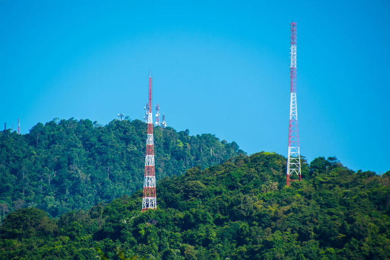 Low angle view of communications tower and trees against clear blue sky