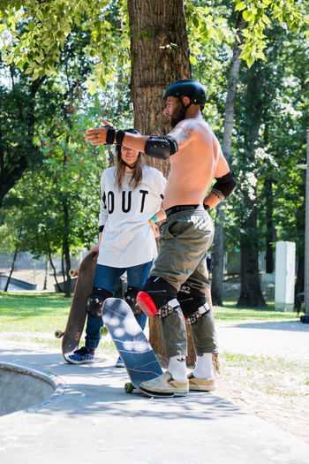 skateboarders Full Length Tree Two People Men Plant Togetherness Casual Clothing Day Real People Leisure Activity People Males  Nature Young Men Sunlight Bonding Young Adult Standing Lifestyles Emotion Outdoors Positive Emotion Couple - Relationship