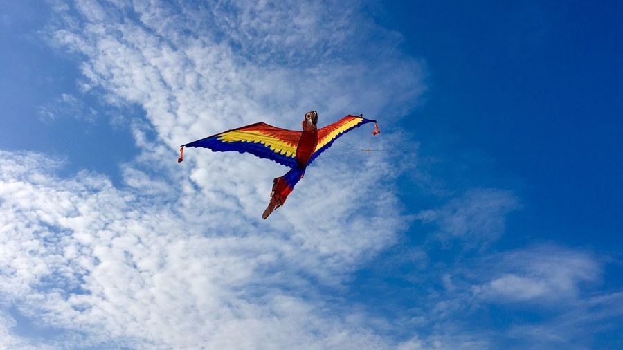 Low angle view of multi colored kite flying against sky