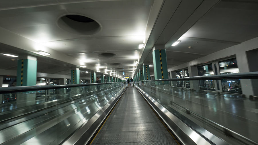 Some people riding flat escalators in the airport terminal of Seoul, South Korea. View from moving walkway Airport Architecture Escalator Hallway Horizontal Illuminated Indoors  Modern Moving Perspective Ride Seoul South Korea Technology Terminal Transport Transportation Travel Travelator Walkway