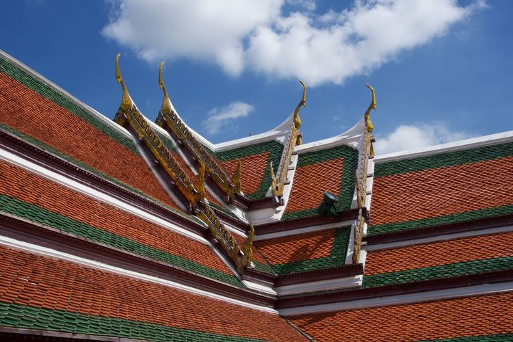Low angle view of ornate thai temple rooftop against sky