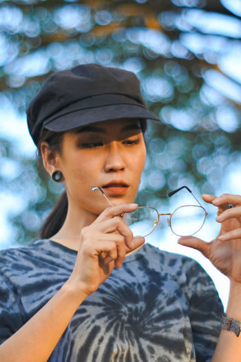 Woman with eyeglasses wearing cap at park