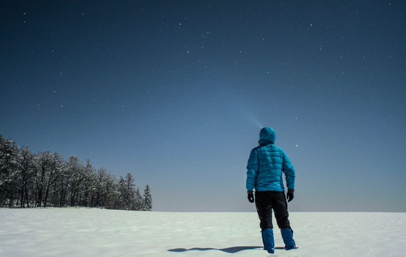 Rear View Of Man Standing On Snow Against Sky At Night
