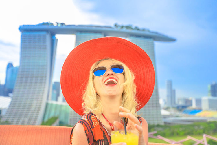 Happy tourist enjoying in travel holiday, Singapore, Southeast Asia. Lifestyle caucasian woman with wide hat drinking aperitif at rooftop. Aerial view or cityscape skyline. Blue sky in a sunny day. Singapore Singapore City Woman Tourist Tourist Attraction  Tourist Destination People Girl Females Aerial View Skyline Cityscape Panorama Happy Travel Hat Lifestyle Enjoy Nature Tourism Smiling Aperitif Drink Orange Juice  Analcolic Glass One Person Architecture Portrait Headshot Sunglasses Glasses Lifestyles Leisure Activity Fashion Front View Young Adult Building Exterior Sky City Food And Drink Focus On Foreground Day Real People Women Hair Outdoors