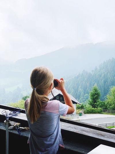 Rear view of girl looking through binoculars