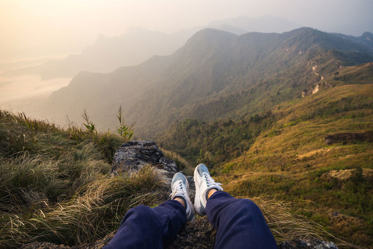 Low section of person relaxing on mountain during sunset