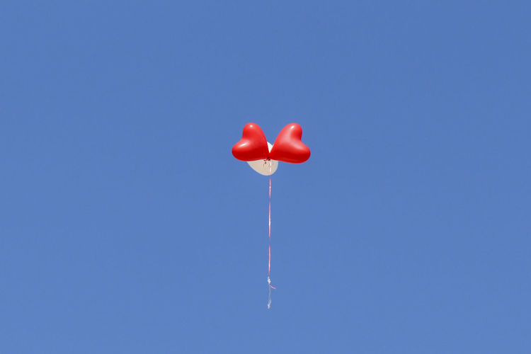 Three Helium Balloons Flying Against Clear Sky