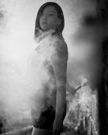 Side view portrait of young woman with smoke standing at park