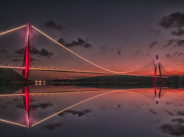 Low angle view of illuminated bridge against sky during sunset