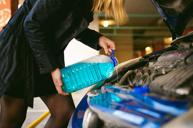 Woman Pouring Oil In Car Engine