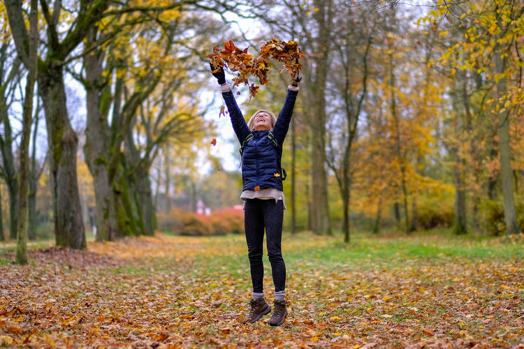 Young woman throwing leaves in a heart shape in the air