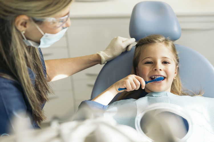 Doctor dentist teaching a child how to brush her Concept Brushing Dental Dentist Dentistry Diagnosis Doctor  Hospital Learning Medicine Teaching Child Clinic Expertise Girl Health Care Kid Medical Odontology Orthodontist  Patient People Professional Teeth Tooth Toothbrush