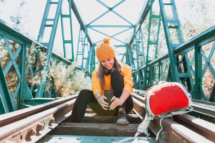 Portrait of young woman sitting on bridge