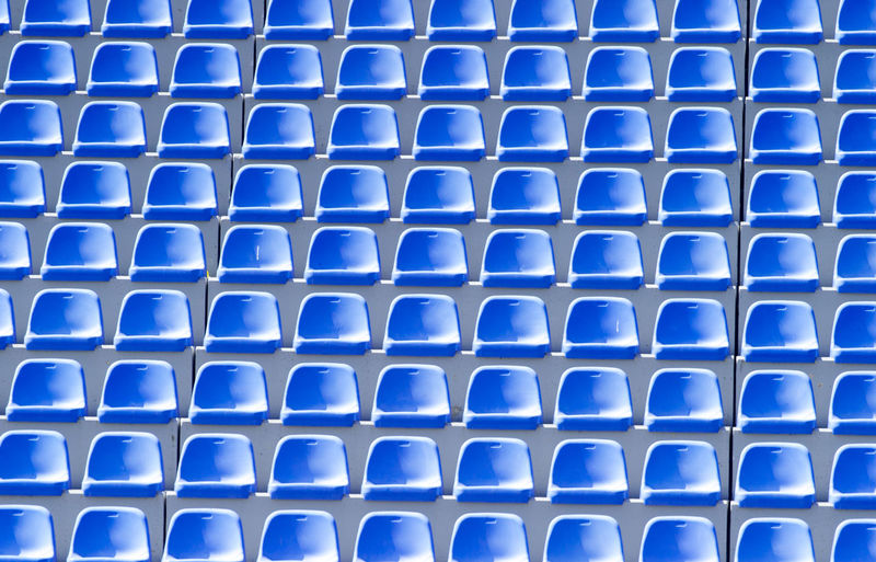 Empty blue plastic chairs in a row at the football stadium Empty Stadium Chair Background Competition Sport Game Play STAND Concert Fans Team Seat Plastic Blue Row LINE Pattern Arena Section Playground Field Theater Club Championship Cup Ground Light Rendering Lamp Electricity  Green Soccer Football Shiny Win Summer Power Floodlit Number Audience Tribune Grand Floodlight Colorful Visit Texture Abstract Spectator Backgrounds Full Frame No People Repetition Side By Side Close-up Metal Textured  In A Row Indoors  Design Grid Geometric Shape Day High Angle View Silver Colored
