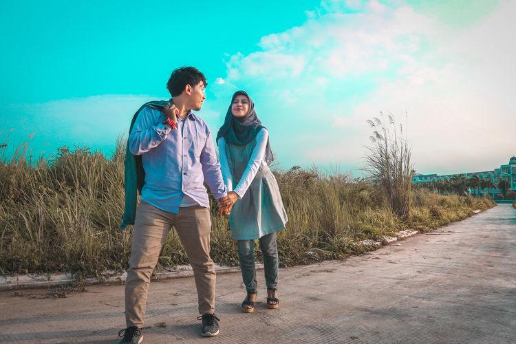 Full length of couple standing on road against sky