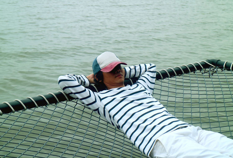 Young man relaxing on net over sea