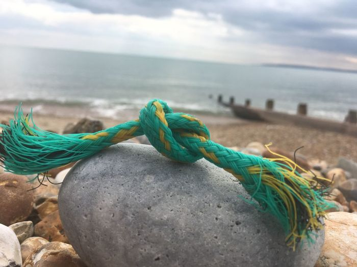 Close-Up Of Rope Tied Up On Beach Against Sky