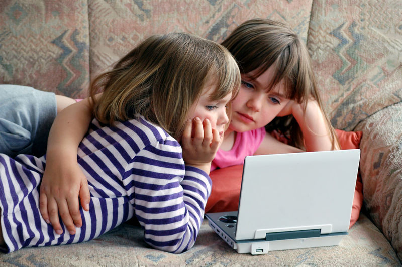 Relaxing Blond Hair Brown Hair Child Childhood Communication Computer Connection Family Females Furniture Girls Hair Indoors  Laptop Offspring Playing Sister Technology Togetherness Two People Using Laptop Watching Movie Wireless Technology