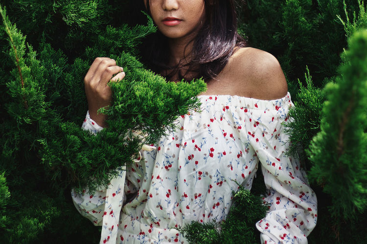 Woman in traditional clothing amidst plants against trees