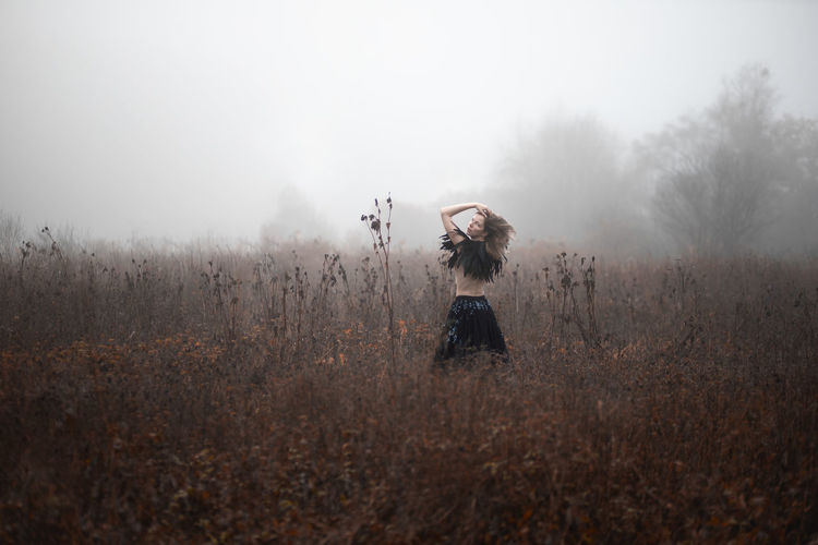Woman standing on field by trees against sky