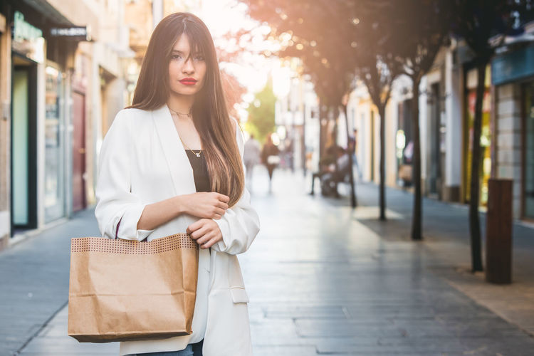 Portrait of young woman with shopping bag standing on footpath in city