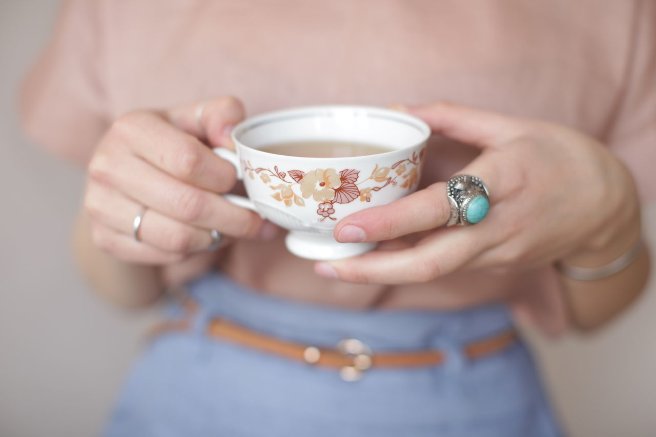 Close-up mid section of a woman holding tea cup