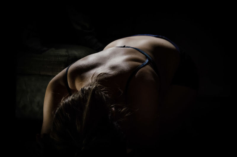 Midsection of woman against black background