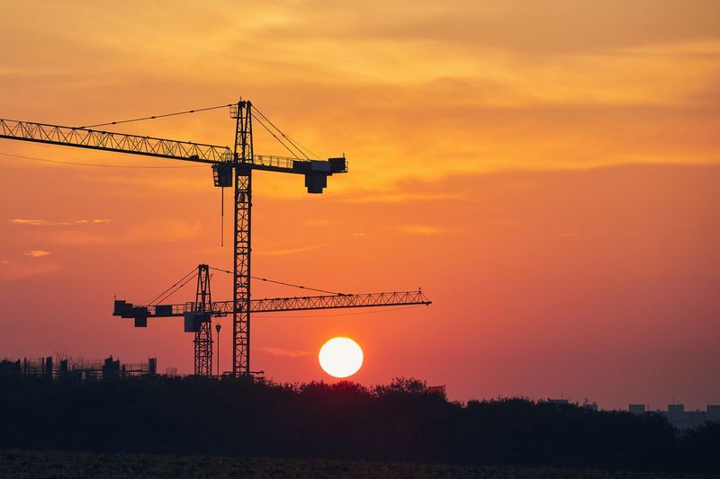 Silhouette cranes at construction site during sunset