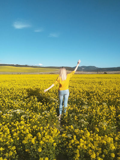 Person standing by yellow flowers on field