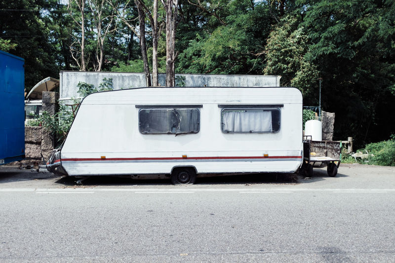 Camper trailer on road against trees