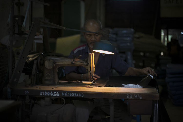 Mature man stitching clothes in workshop