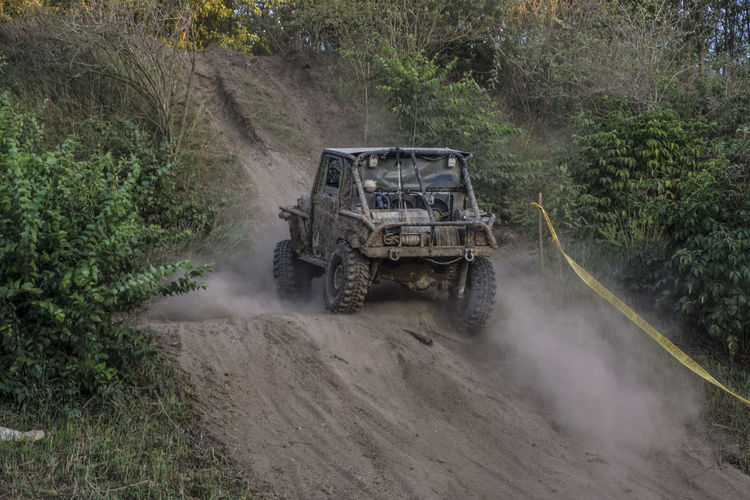 Jeep going uphill on dusty hill