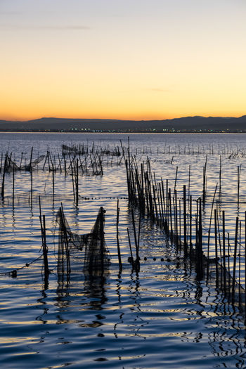 Wooden posts in sea at sunset