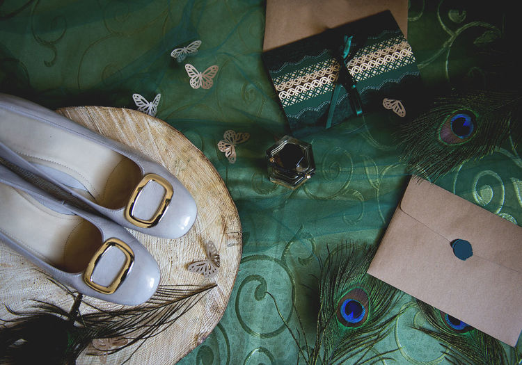 Directly above shot of peacock feathers and shoes on table