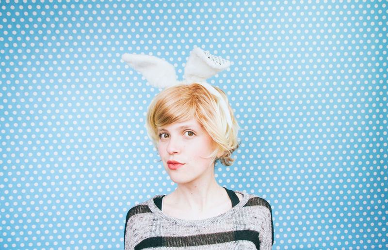 Portrait Of Young Woman Wearing Costume Rabbit Ears Against Blue Polka Dots Wall