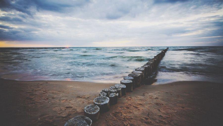 Stepping stones on calm beach against cloudy sky