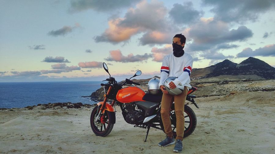 Man riding motorcycle on beach against sky
