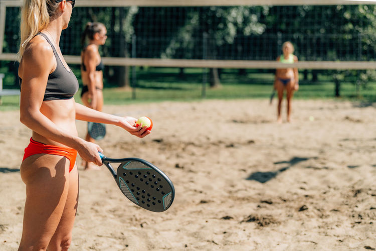 Female friends playing beach tennis