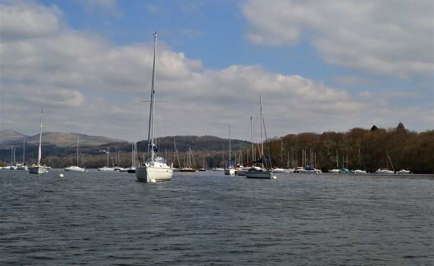 Sailboats on Lake Windermere with the fells of the Lake District rising up behind on the mainland, Windermere, Cumbria, UK Nautical Vessel Water Transportation Mode Of Transportation Sailboat Sky Cloud - Sky Waterfront Pole Sea Mast Nature Day Beauty In Nature Sailing Scenics - Nature No People Outdoors Tranquil Scene Yacht Marina Windermere Cumbria Masts Lake District Fells