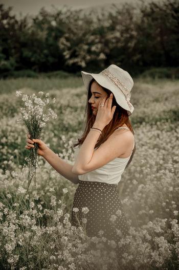 Woman wearing hat standing on field