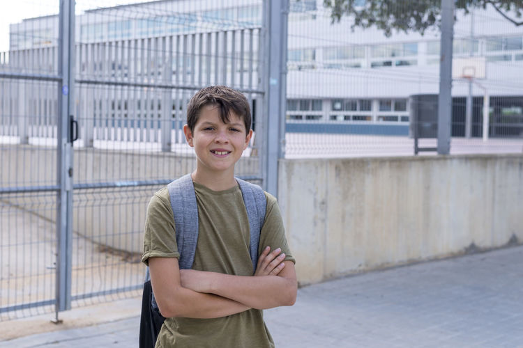 Portrait of boy with arms crossed standing against school
