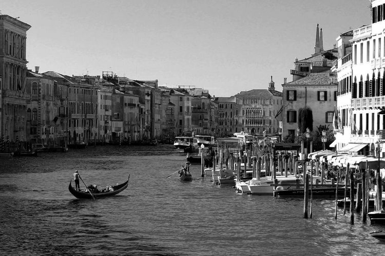 Gondolas in grand canal amidst buildings against clear sky