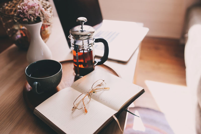 relaxing at home with laptop, hot tea and notebook. Cozy weekend morning, modern lifestyle. Table Indoors  Drink Cup Food And Drink No People Still Life Coffee Coffee - Drink Book Teapot French Press Reading Notes Planner Planning Work Routine Home Office Morning Cozy Relaxing Lazy Glasses