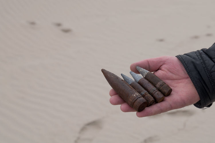 Cropped Hand Holding Rusty Bullets At Beach